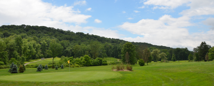 Panoramic view of golf course and tree-covered hills