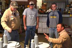 Co-op lineworkers explain job to two high school students