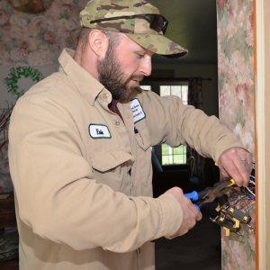 Valley REC electrician using pliers to improve wiring