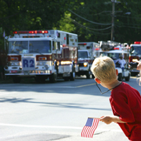 A boy watching a parade of emergency vehicles